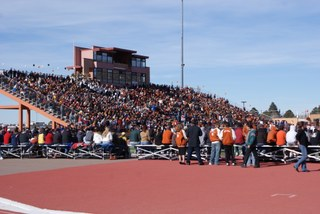 The stadium with the bleachers filled with sports fans.