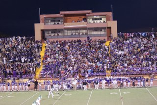 The stadium at night during a football game with the bleachers filled with sports fans.
