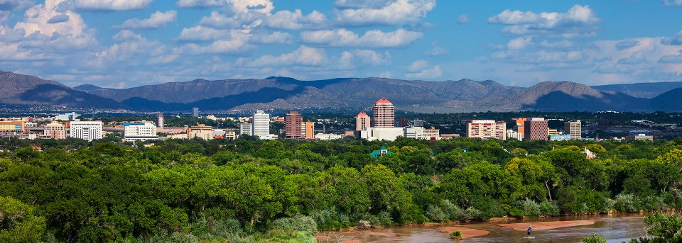 Panorama view of downtown Albuquerque with the Rio Grande in the foreground.