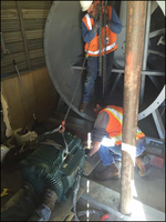 Two M&O employees replacing a large motor