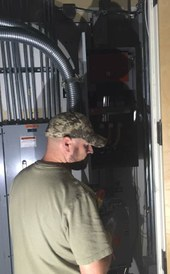 An M&O technician working on an electrical upgrade