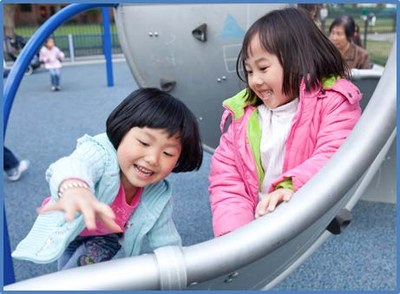 Two girls laughing and playing on a slide