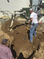 Heavy equipment operator assists in replacing a water line