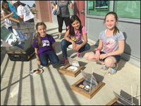 Students smiling with their handmade solar ovens
