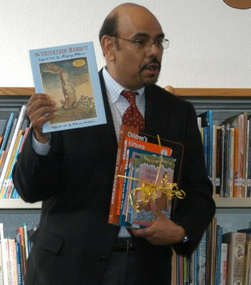 Ramon Gonzales, PNM vice president of people services, gives Zuni Elementary students a stack of books.
